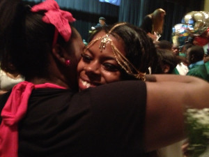 Monae Robinson at her high school graduation, receiving a hug from a loved-one.